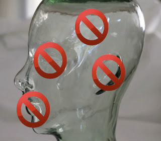 glass head sculpture with cancel symbols over mouth, eye brain and ear.