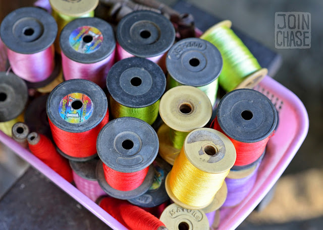 Colorful thread in a basket on a wooden loom in rural Sagaing Division, Myanmar.