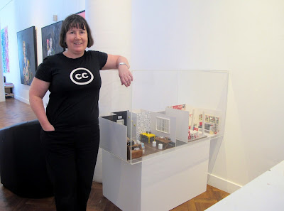 "Woman standing next to a display caseWoman standing next to a display case in a gallery with two 1/12 scale miniature scenes in it"" one a cafe, and one a holiday cottage. with two 1/12 scale miniature scenes in it"" one a cafe, and one a holiday cottage."