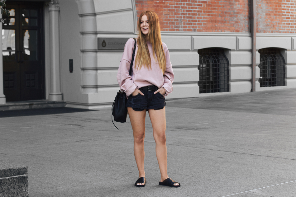 Pink oversized sweater, GRLFRND slouchy shorts, bucket bag, The Mode Collective Dilan slides