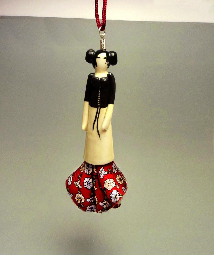 collier avec pendentif petite sculpture de femme et robe en soie