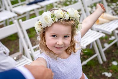 Niña vestida para una boda con una coronita de la mano de su padre