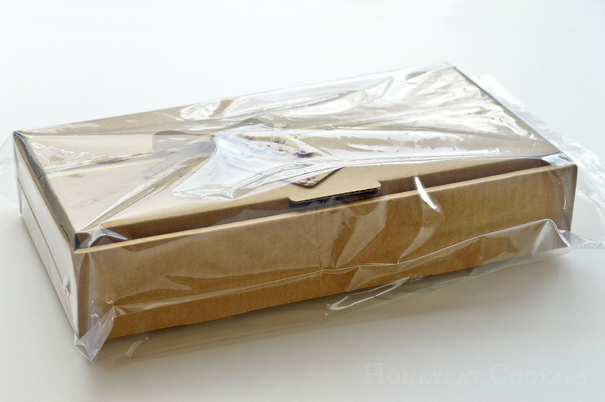 Decorated cookie gift box wrapped in plastic prior to shipping, photo by Honeycat Cookies