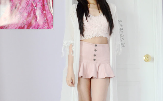 A sweet pastel summer outfit featuring a pink lace bralette from Dresslink, faux suede buttoned skort, and white tasseled kimono.