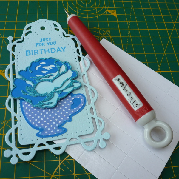 Altenew layered rose flower die from Simply Cards and Papercraft magazine in blue in a teacup die placed onto a blue tonic studios tag for birthday card