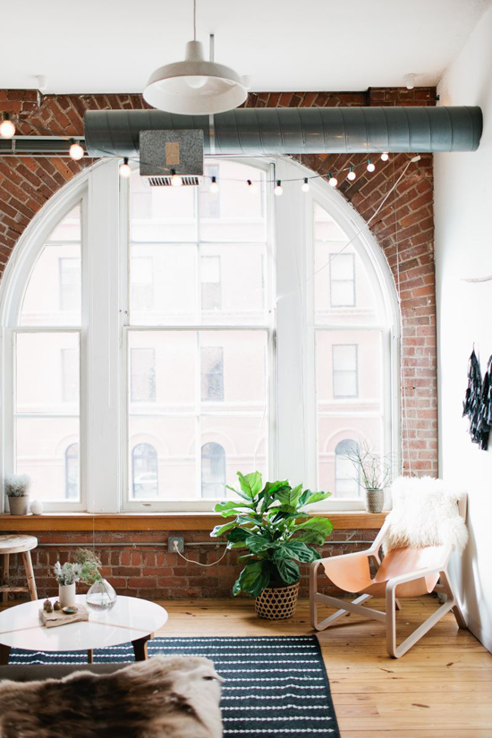 Exposed brick walls and large windows in the house of Madelynn Furlong. Photo by Wing Ta via The Everygirl.