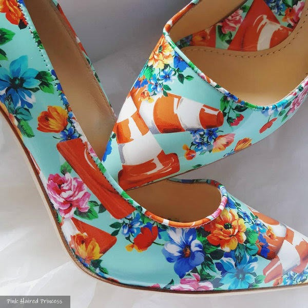 close up of traffic cone and floral printed shoes in box