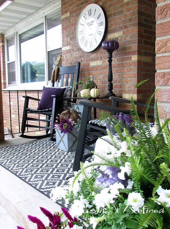 Using a timeless black and white color scheme with pops of fall color really spruces up this small and cozy front porch for Fall.