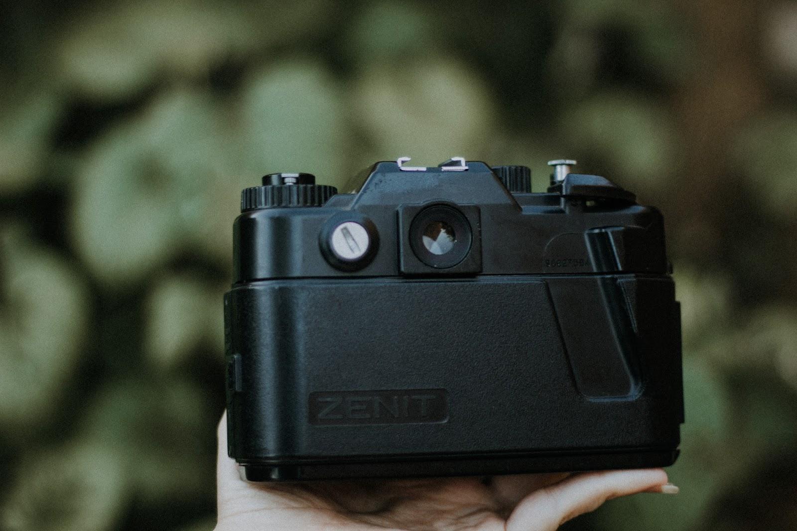 Comprei: Zenit 122. Ali temos o anel de foco com a escala amarela em metros, em outras lentes além da escala em metros, aparece também a escala em pés. No meio em verde, temos a profundidade de campo, segundo a abertura do diafragma que está sendo usado.