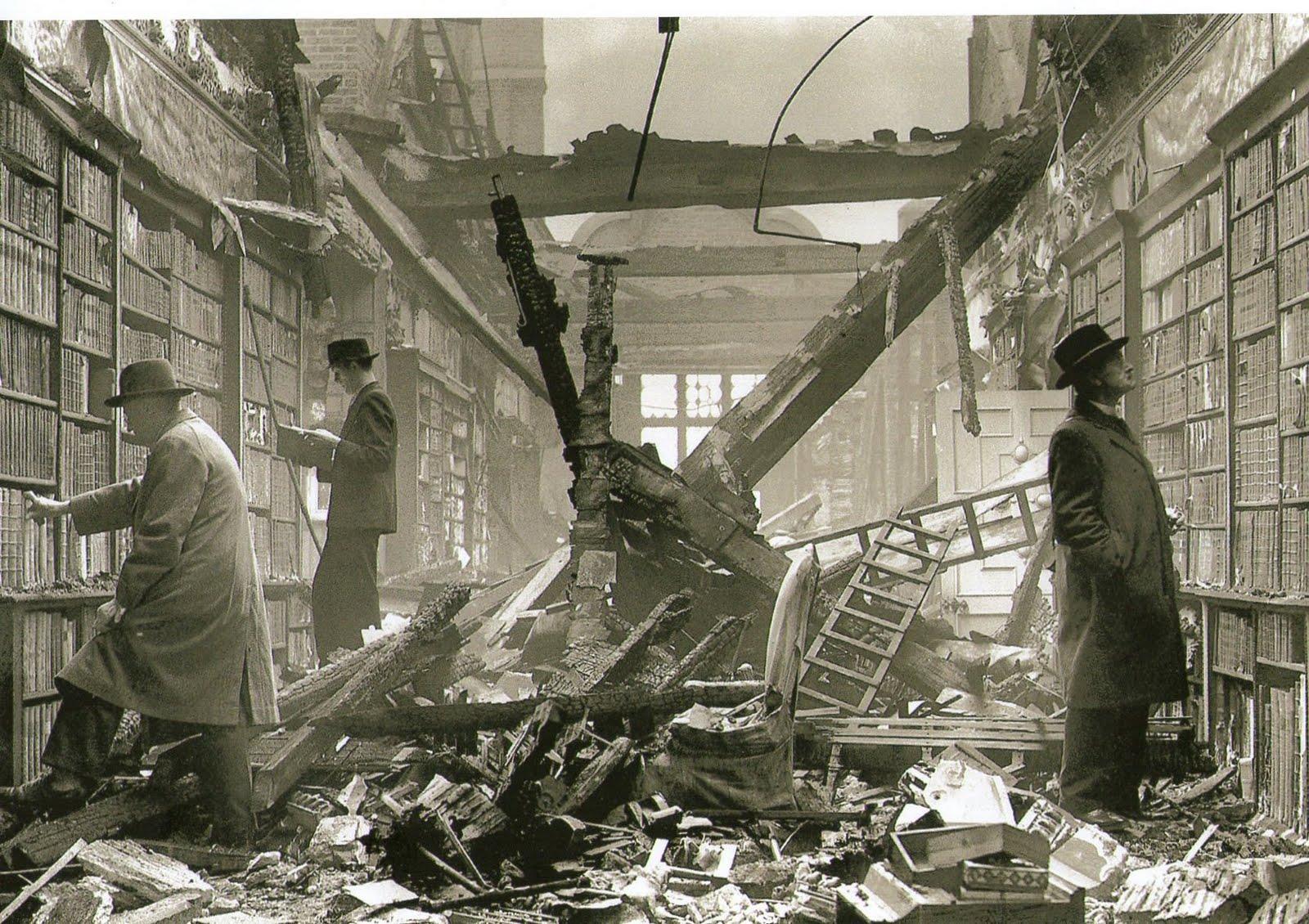 Een foto van een gebombardeerde bibliotheek in Londen. Ondanks de traumatiserende gebeurtenissen lijkt de werkdruk laag en het werkplezier aanwezig bij deze mannen die rustig een boek uit de kast zoeken.