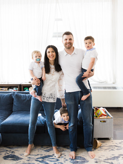 parents and three young sons standing together for at home family portraits