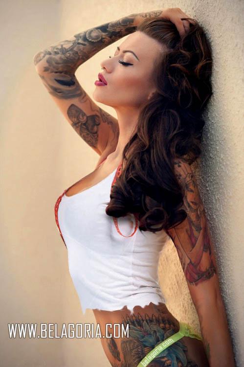 mujer apoyada en una pared, lleva camiseta rota, y tatuajes por el cuerpo