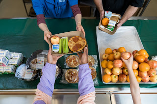 Student Nutrition Services staff hand lunches to students in a cafeteria.