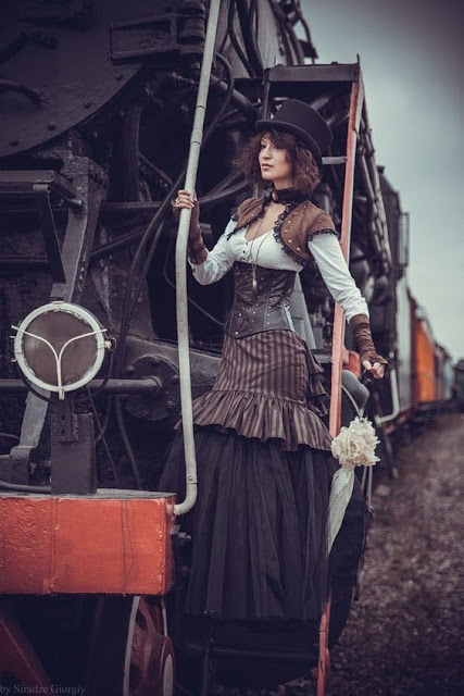 Woman dressed in steampunk clothing, on the side of a steam train. Striped trumpet skirt, corset, bolero jacket, top hat, parasol.