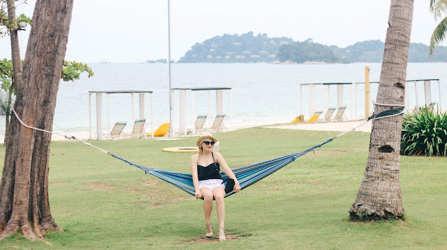 Fashion and Travel Blogger GlobalFashionGal (Brianna Degaston) wearing a black One Piece Swimsuit while sitting on a hammock at a resort in Bintan Island, Indonesia.
