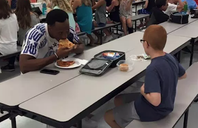 Florida State football player Travis Rudolph, a Black man with  short natural hair, eating pizza in a school cafeteria at a table with a  white boy with very short red hair and glasses, who is seen from behind.
