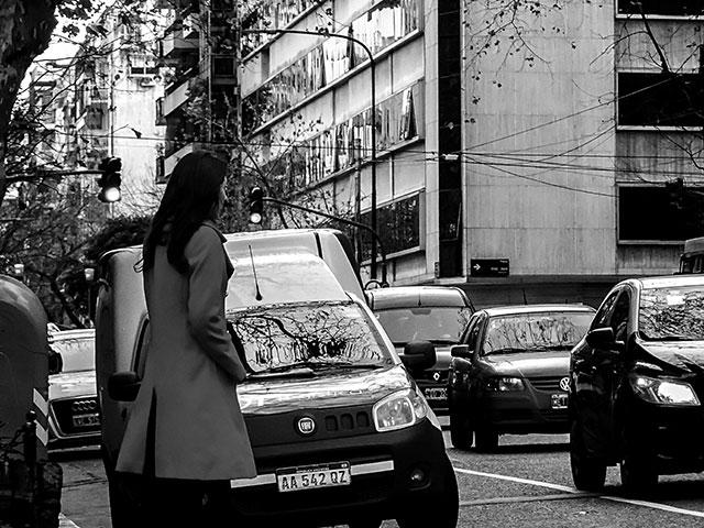 BYN.Una joven con tapado esperando cruzar la calle.