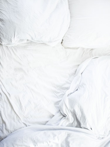 Messy bed with white sheets
