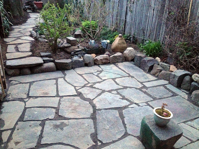 """Reclaimed slate backyard patio Artist and Builder laying out slate complete with loose dry """"grout"""""""