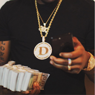 Davido Poses With 10 Wads Of 100 Dollar Bills