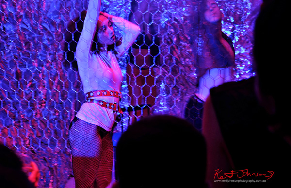 Dancers behind wire mesh, blue light. Tony Mott book launch Alphabet A-Z Rock 'N' Roll Photography. Photo by Kent Johnson