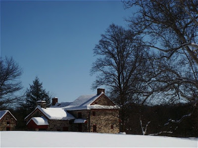 Stone house with snow on roof, bare trees, and snow covered field