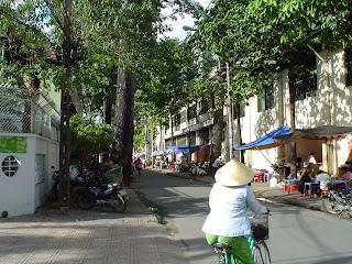 Woman on bicycle with Vietnamese hat. Ho Chi Minh City (Saigon)