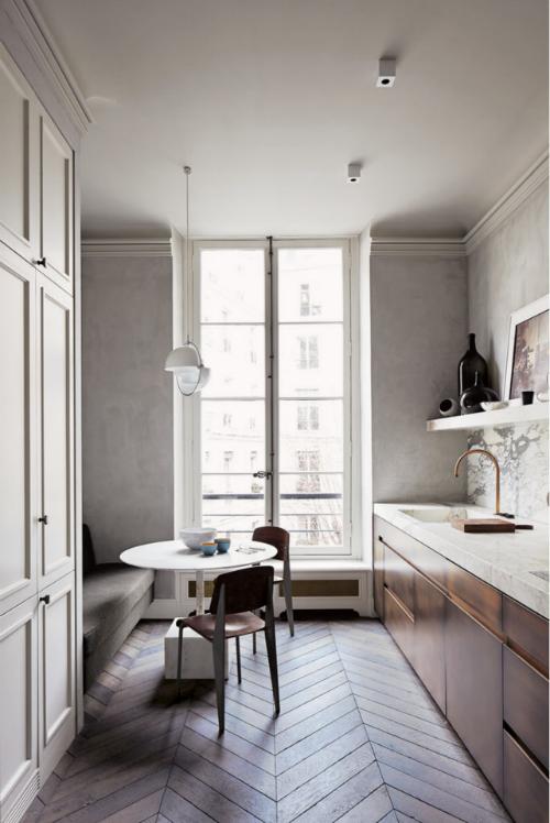 In der Küche ist Parkett verlegt, die Küchenzeile ist bronzefarbend und hat eine Marmorplatte