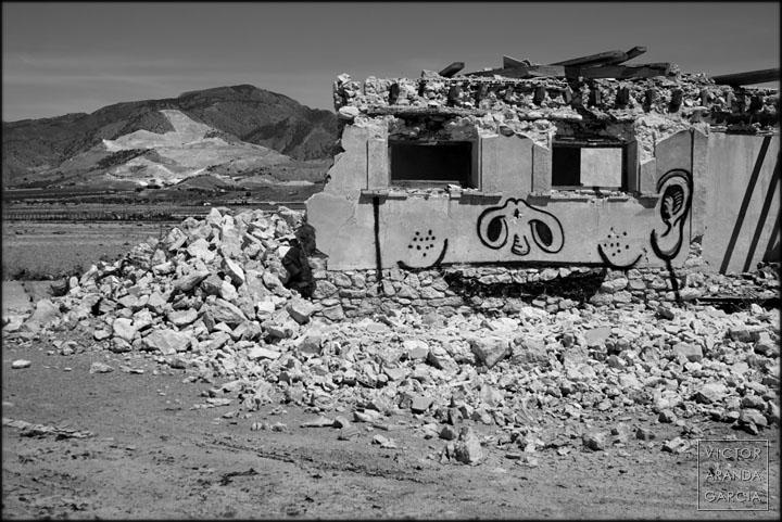 Fotografia de una casa en ruinas con un grafiti y una montaña con una cantera al fodo