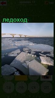 по реке начался ледоход, льдины плывут по воде перед мостом