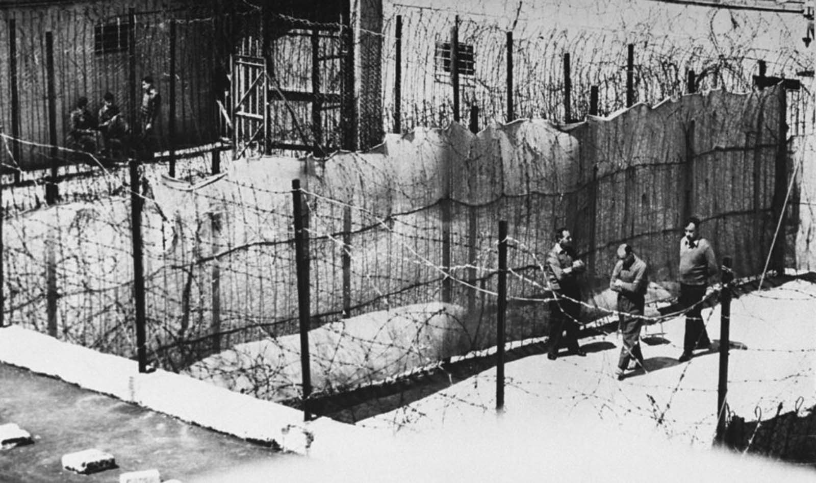 Barbed wire his victims once knew confined Eichmann's walks.