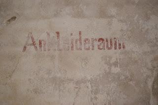 """An einer weißen Wand steht in Teils verwitterten Buchstaben das Wort """"Ankleideraum"""""""