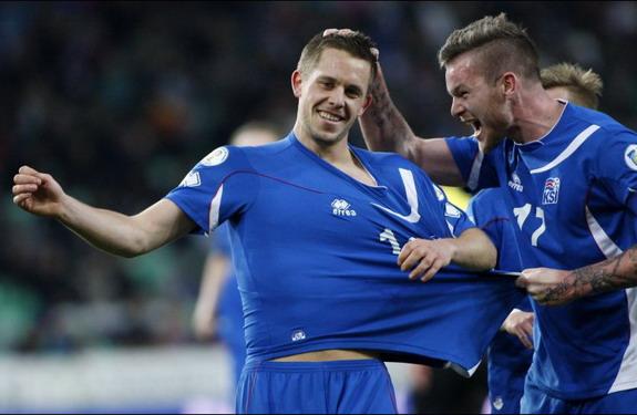 Iceland player Gylfi Sigurðsson celebrates with teammates after scoring against Slovenia