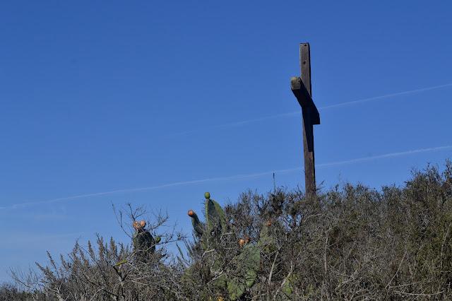 below the cross