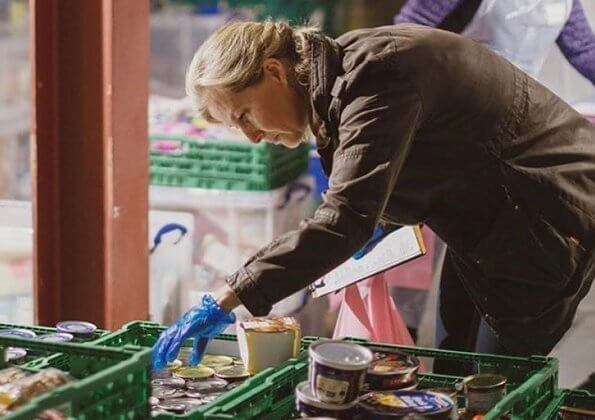The Countess of Wessex visited the warehouse facility of the Woking Foodbank at Sheerwater. brown coat and pink sweater