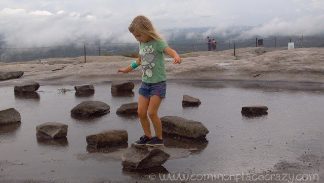 Little girl balancing on a rock in the middle of a puddle