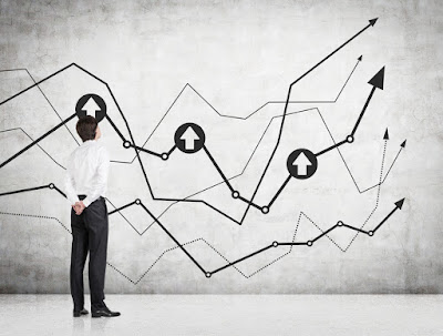 a man stands looking at a graph of multiple arrow all going upward