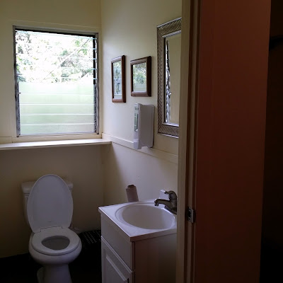 A clean spacious bathroom, toilet, and sink area.