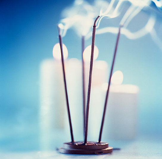 Incense burning with candles in the background
