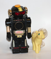 [Image: A black toy robot standing next to a My Little Pony. The robot has golden ears and arms, a speaker on its chest, and a big round button on top of its head. On its belly, it has a symbol referring to nuclear power. Text around the robot says OMNI, 024-2931:1524, and 2 MODEL-B.]