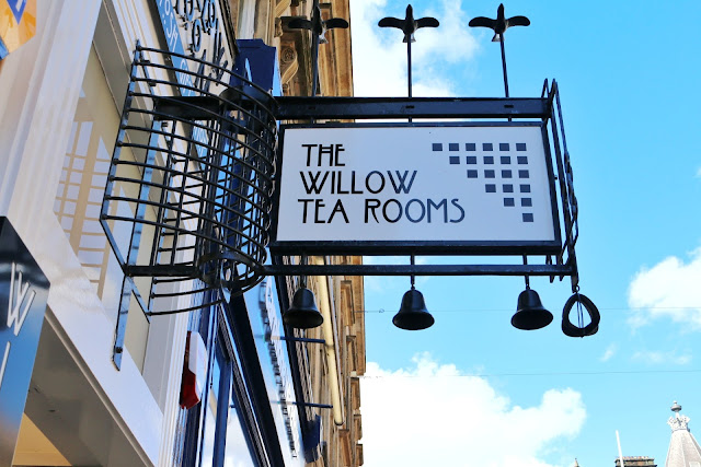 A close up shot of The Willow Tea Rooms In Glasgow city centre, white sign with some rennie mackintosh designs in black along with the name