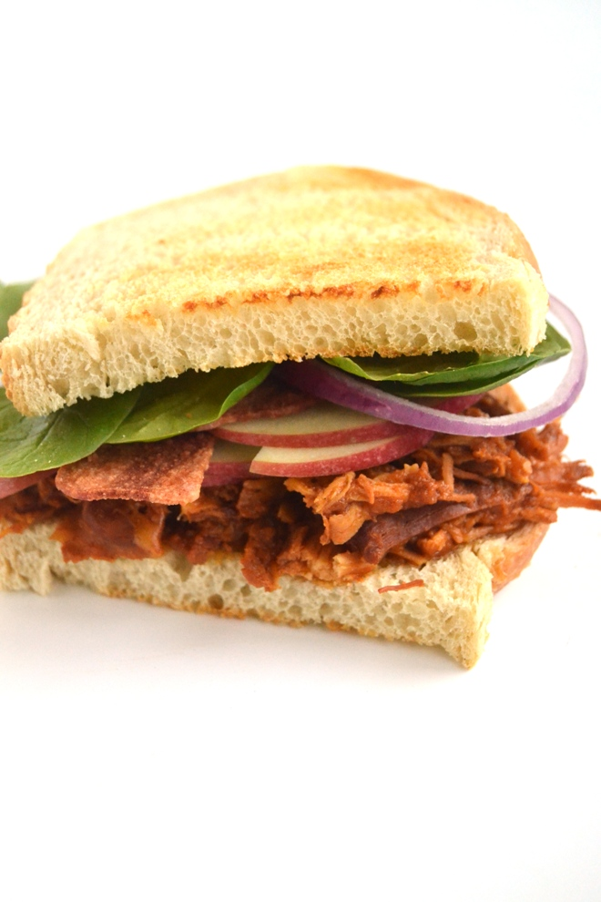 Slow-Cooker Apple Barbecue Chicken Sandwiches are loaded with slow-cooked shredded chicken with homemade BBQ sauce, thinly sliced apples, melted cheddar cheese, red onion, bacon and spinach all on top of toasted sourdough bread! www.nutritionistreviews.com