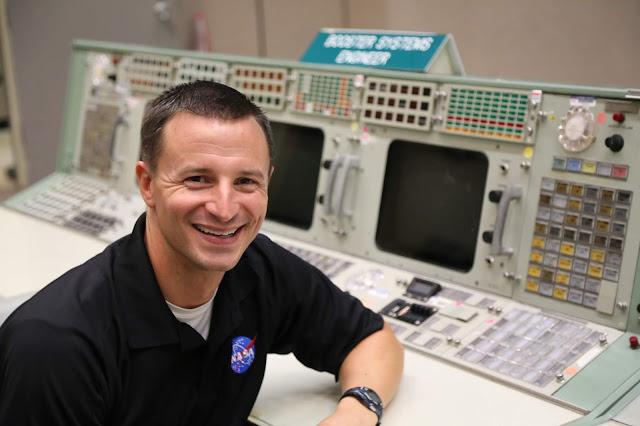 a man in a NASA polo sits by a control panel