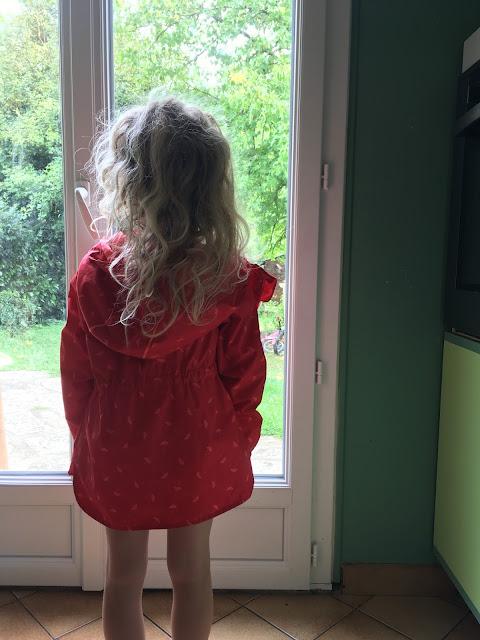 une adorable petite fille en manteau rouge semble vouloir sortir dans le jardin