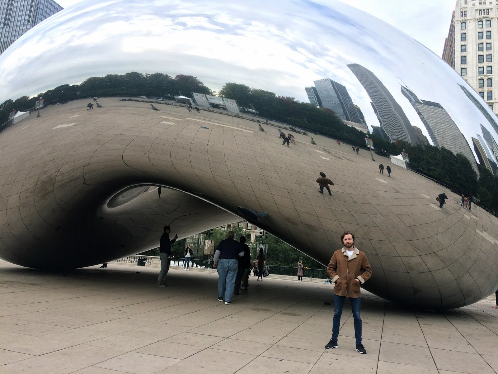 Person standing in front of a huge reflective sculpture in Millenium Park, Chicago