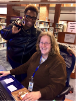 Ms. Simone standing next to an Olney Librarian who is seated at a computer