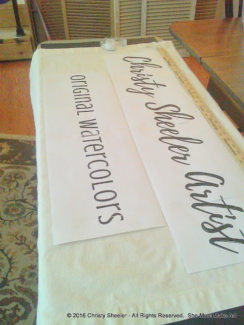 Text is printed on paper and laid out on the fabric to judge how it fits.
