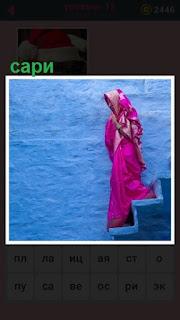 девушка спускается по лестнице в сари розового цвета