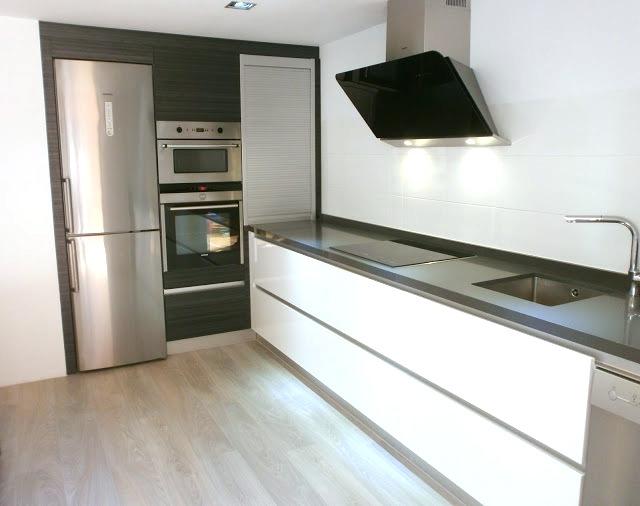 Abierta y con isla una cocina que invita a compartir for Cocina blanca encimera negra