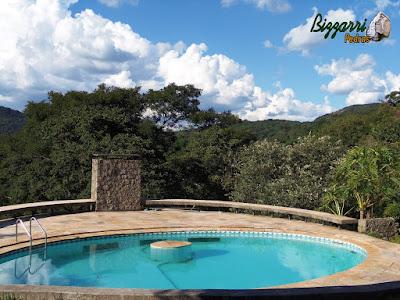 Construção da piscina com parede de pedra da chaminé da lareira do salão de festas que fica em baixo da piscina com os bancos de concreto em volta da piscina e o piso com pedra São Tomé.